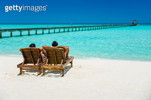 Couple enjoying holidays sitting on lounge chairs at tropical paradise beach at Dhiffushi Holiday island at South Ari atoll, Maldives. Beautiful turquoise Indian ocean sea with white sand. Luxury travel holidays background. Model and Property released. - gettyimageskorea