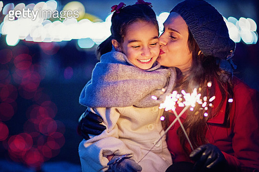 Mother is kissing her daughter at Christmas - gettyimageskorea
