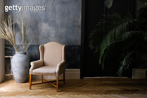 Beige chair and a large vase near the window in the hall, next to a palm tree near the door. - gettyimageskorea