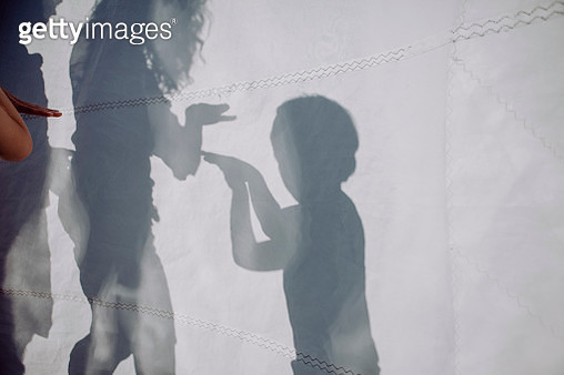 Family doing a shadow play behind sail - gettyimageskorea