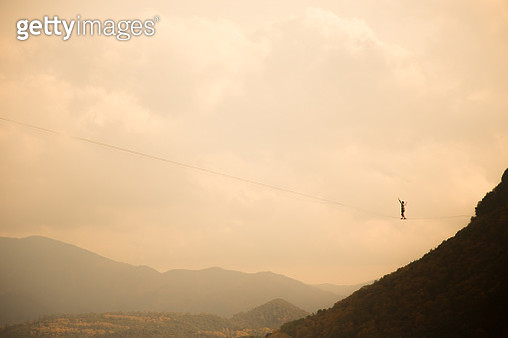 Tightrope walker in a stunning outdoor nature walking between two cliffs over the nature with nice sky. - gettyimageskorea