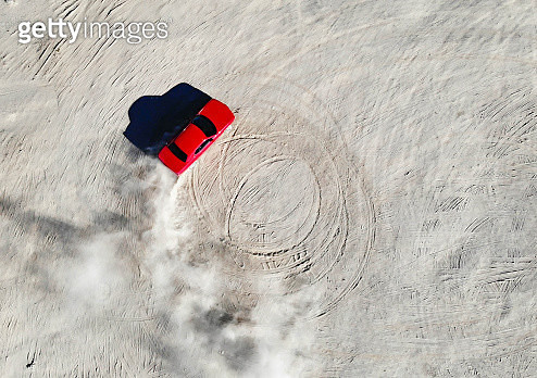 Aerial view of red muscle car doing donuts in the desert of California. - gettyimageskorea