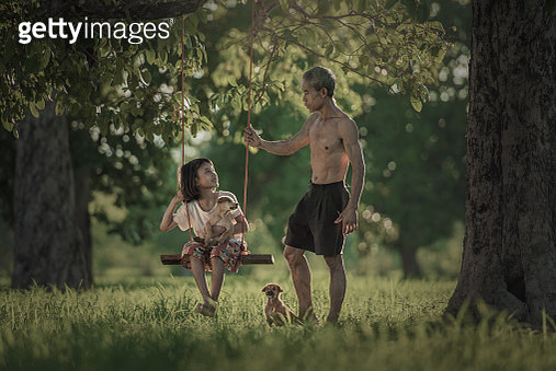 Girl (6-7) sitting on swing with puppy and talking with father - gettyimageskorea