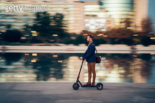 Profile view of businessman riding a scooter on his way to work - gettyimageskorea