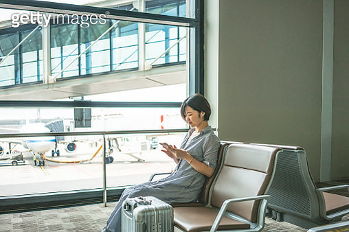 The women looking at smartphone at airport while waiting for flight - gettyimageskorea