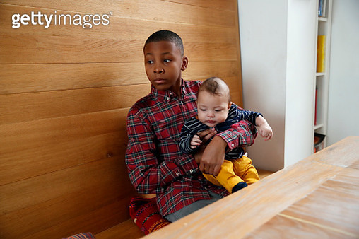 Boy holding baby brother at kitchen table - gettyimageskorea
