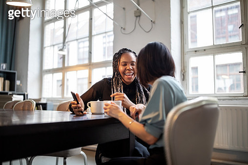 Women having fun conversation during coffee break in office - gettyimageskorea
