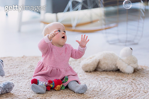 Shot of an adorable baby girl sitting with her toys on the carpet in the living room - gettyimageskorea