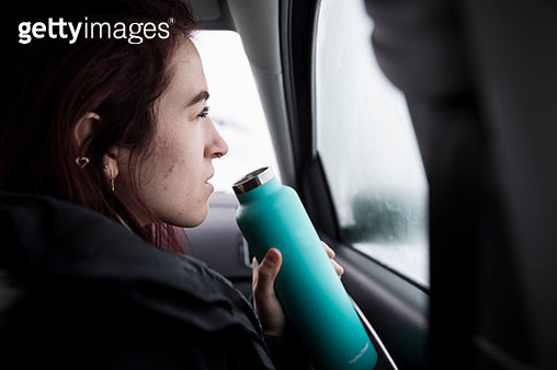 Portrait of young woman driving inside car with water bottle - gettyimageskorea