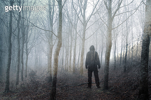 An artistic, double exposure of a hooded man standing in a spooky forest on a foggy winters day. With a grunge, blurred edit. - gettyimageskorea
