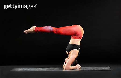 Full Length Side View Of Woman Performing Yoga Against Black Background - gettyimageskorea