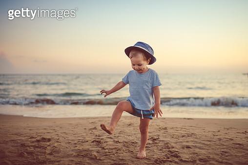 Happy child enjoying sunset near the sea - gettyimageskorea