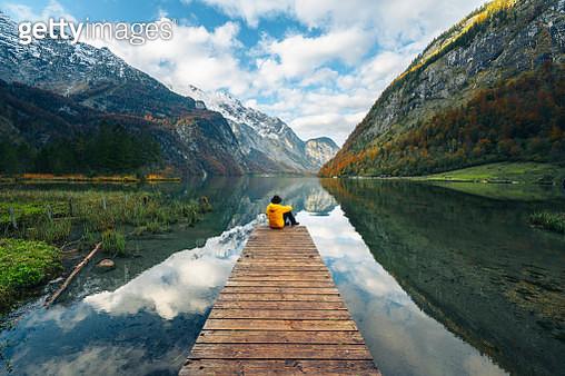One man sitting on a boat pier admiring the Konigssee lake, Bavaria, Germany - gettyimageskorea