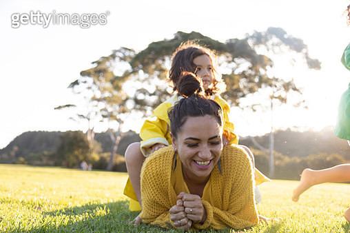 Mother laughing as one daughter is sitting on top of her and the other is running - gettyimageskorea