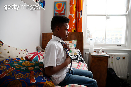 Boy sitting on bed tying a tie - getting ready for school - gettyimageskorea