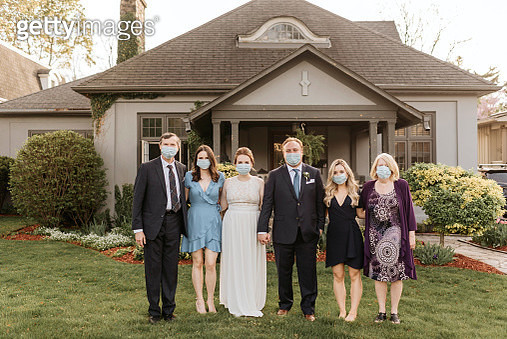 Wedding party posing for group portrait on front lawn, wearing face masks during Coronavirus crises. - gettyimageskorea