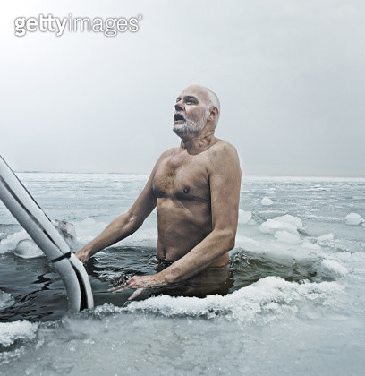 62 yr old man dipping his body in minus 2 degree sea water on the coast of Denmark. - gettyimageskorea