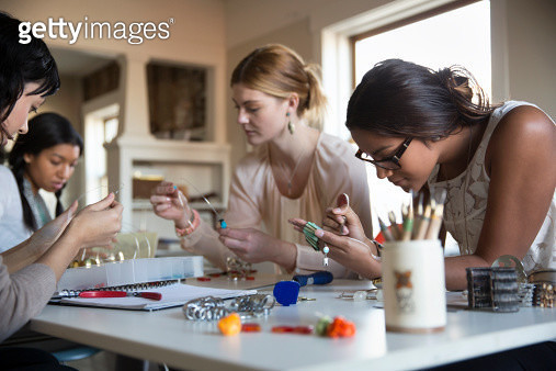 Female colleagues making bracelet and necklaces at desk - gettyimageskorea