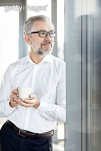 Businessman with cup of coffee looking out of window - gettyimageskorea