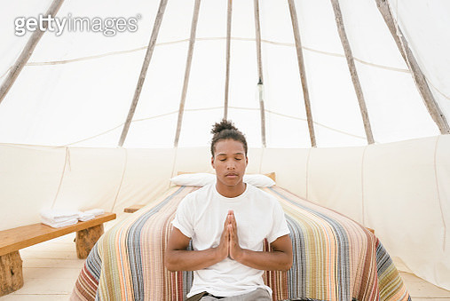 Young man meditating in teepee - gettyimageskorea