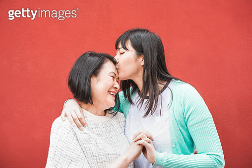 Smiling Young Woman Kissing Mother While Holding Hands Against Red Wall - gettyimageskorea