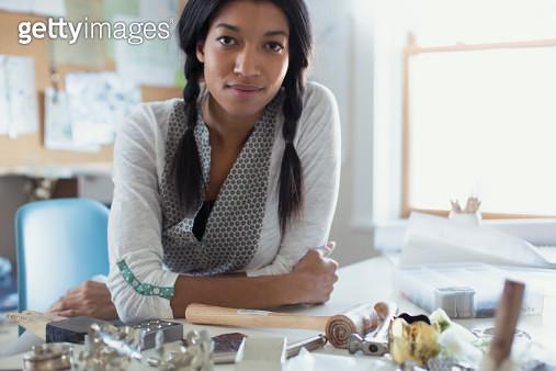 Portrait of mid adult female artist sitting with work tools on desk - gettyimageskorea