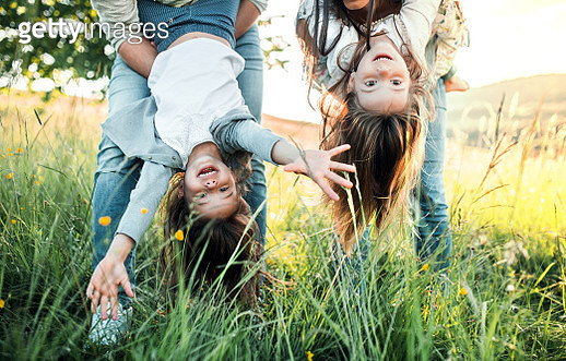 Unrecognizable parents playing with daughters on a meadow on a sunny day. - gettyimageskorea