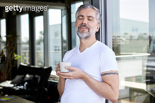 Man standing at French enjoying cup of coffee - gettyimageskorea