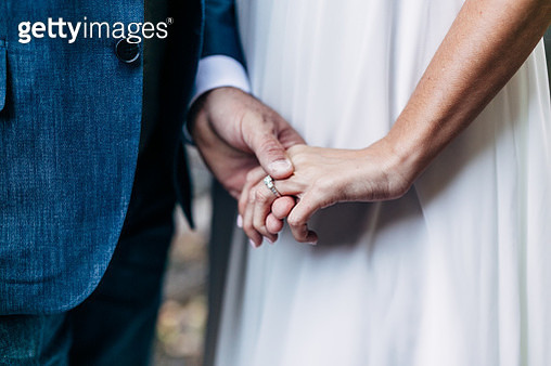 Midsection Of Newlywed Couple Holding Hands - gettyimageskorea