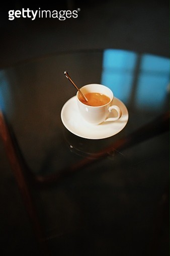 Illustration of a white coffee cup, with a metallic spoon, on a glass table. The reflection of a window is seen on the table. - gettyimageskorea