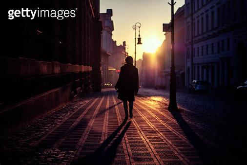 Rear View Of Silhouette Woman Walking On Street In City - gettyimageskorea