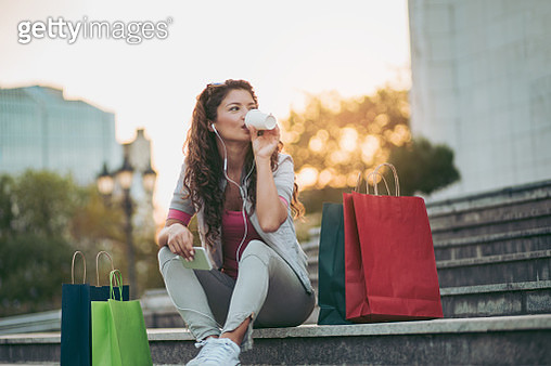 Young woman resting after shopping and listening to music - gettyimageskorea