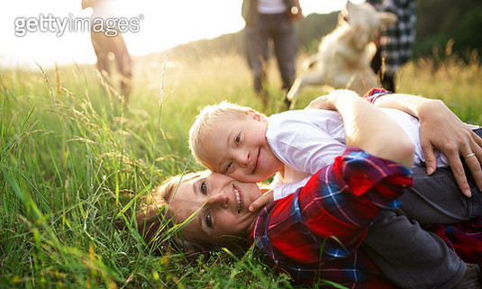 Close-up of mother with down syndrome child resting on grass in nature. - gettyimageskorea