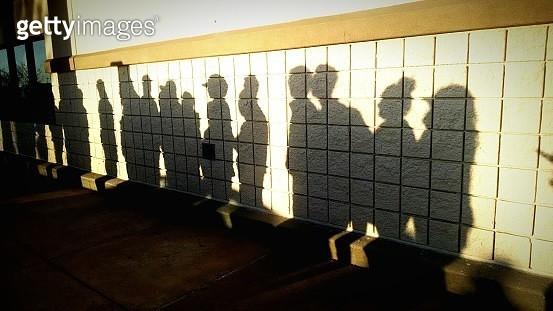 Shadow Of Men And Women Standing In Queue On Wall - gettyimageskorea