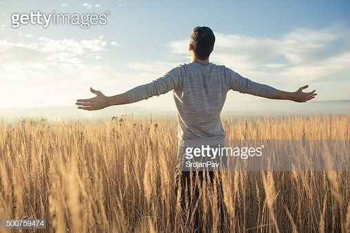 Young caucasian man standing in the middle of a prairie with his arms outstretched, enjoying a beautiful sunny day in the nature. - gettyimageskorea