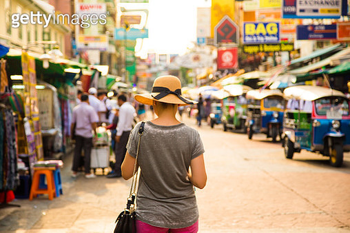 Traveler girl with hat protecting from strong sun in the bustle city of Bangkok during travel vacations. - gettyimageskorea