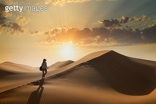 A young woman climbing a giant sand dune in a desert at sunset in the Empty Quarter, or Rub al Khali,  the world's largest sand desert - gettyimageskorea