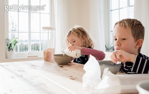 brother and sister eating breakfast at home before school - gettyimageskorea