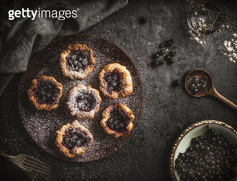 Small cakes on wooden plate with a black currant and jam - gettyimageskorea