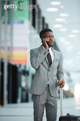 Black businessman speaking on phone in airport - gettyimageskorea