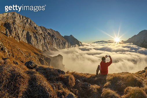 Mountain Climber take picture with mobile Phone at sunrise - Alps - gettyimageskorea