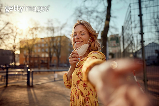 Red-haired woman wearing a FFP2 face mask in the city - gettyimageskorea