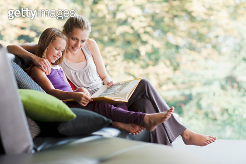 Mother and daughter reading storybook - gettyimageskorea