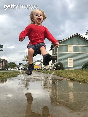 Full Length Of Boy Jumping Over Puddle Against Sky - gettyimageskorea