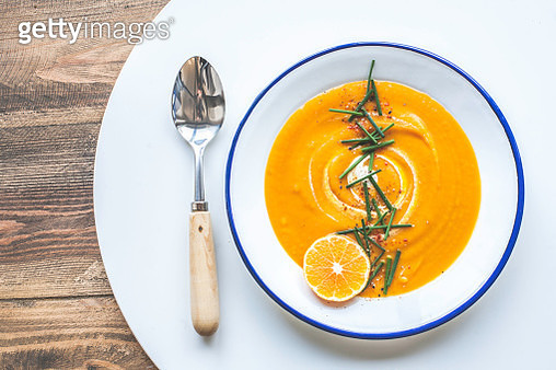 A bowl of silky, butternut squash/ pumpkin soup with cashew cream, citrus and chives. - gettyimageskorea