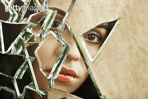 Close up of a woman looking through broken glass - gettyimageskorea
