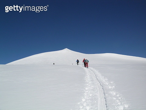 Rear View Of People Walking On Snowcapped Mountain Against Clear Sky - gettyimageskorea