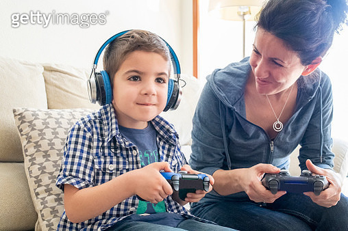 Mother and son Playing on console with Videogames joystick - gettyimageskorea