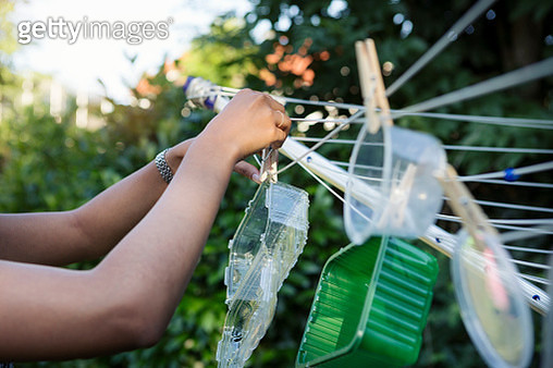 Young woman hanging washed plastic containers onto a clothesline to dry - gettyimageskorea