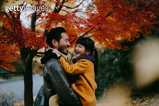 Father holding cheerful little girl under autumn leaves, Tokyo, Japan - gettyimageskorea